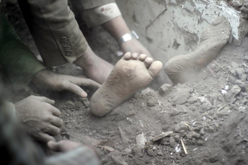 The feet of a child covered in dust as people search for survivors under the rubble of a house destroyed by an air strike in Sanaa, September 2015