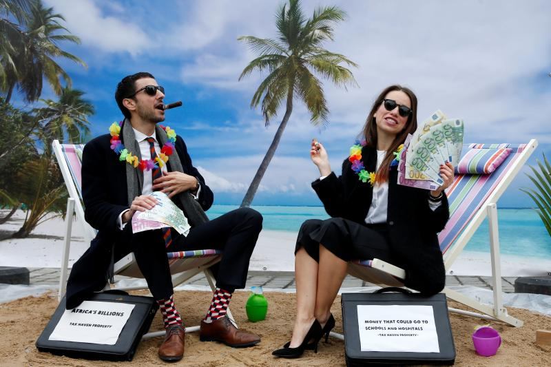 Activists stage a protest on a mock tropical island beach representing a tax haven outside a meeting of European Union finance ministers in Brussels, Belgium, December 2017.