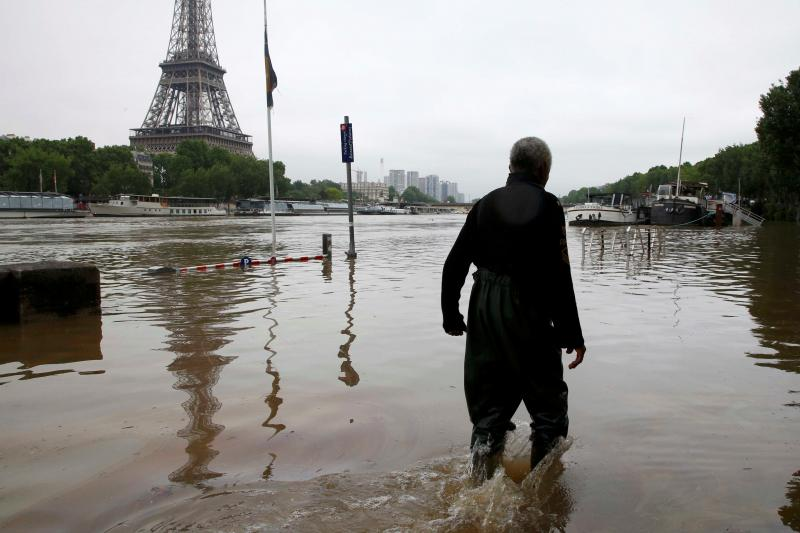 A man walks on a flooded road near his houseboat moored near the Eiffel towel during flooding on the banks of the Seine River in Paris, France, after days of almost non-stop rain caused flooding in the country, June 2016.