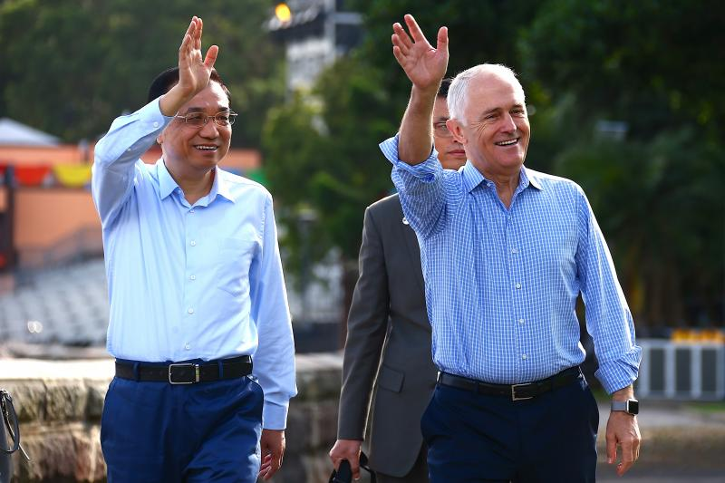 Australian Prime Minister Malcolm Turnbull waves with Chinese Premier Li Keqiang to members of the public as they walk along the Sydney Harbour foreshore in Australia, March 2017.
