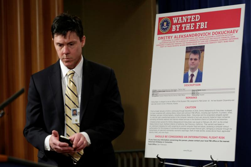 A Department of Justice staffer stands near a wanted poster of a Russian hacker in Washington, D.C., March 2017.