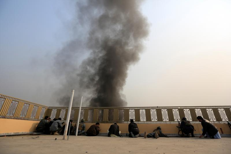 Afghan policemen take position during a blast and gun fire in Jalalabad, Afghanistan, January 2018.