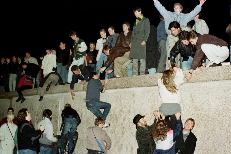 East Germans climb the Berlin Wall at the Brandenburg Gate to celebrate the opening of the border, November 1989.