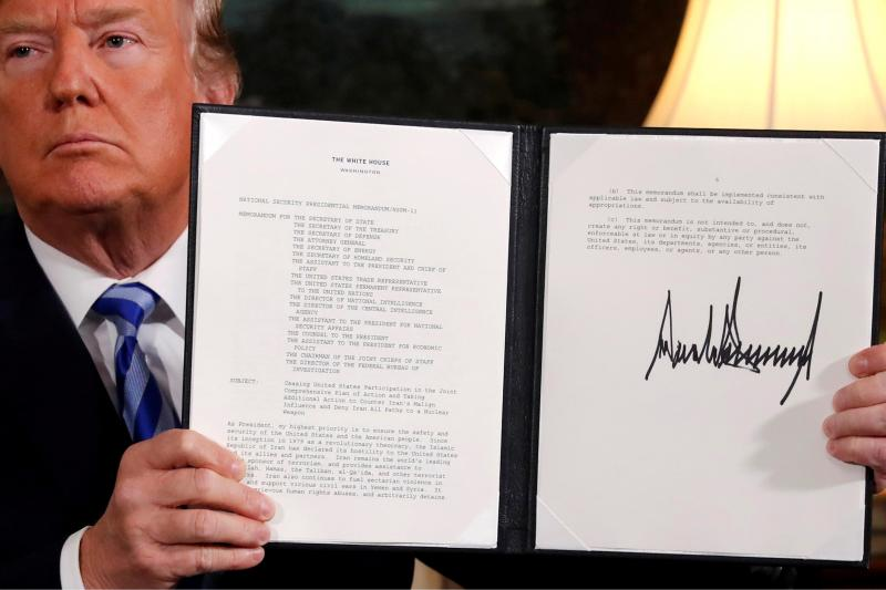 U.S. President Donald Trump holds up a proclamation declaring his intention to withdraw from the JCPOA Iran nuclear agreement after signing it in the Diplomatic Room at the White House in Washington, May 2018.