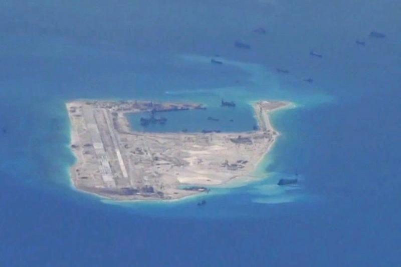 Chinese dredging vessels are purportedly seen in the waters around Fiery Cross Reef in the disputed Spratly Islands in the South China Sea in this still image from video taken by a P-8A Poseidon surveillance aircraft provided by the United States Navy, Ma