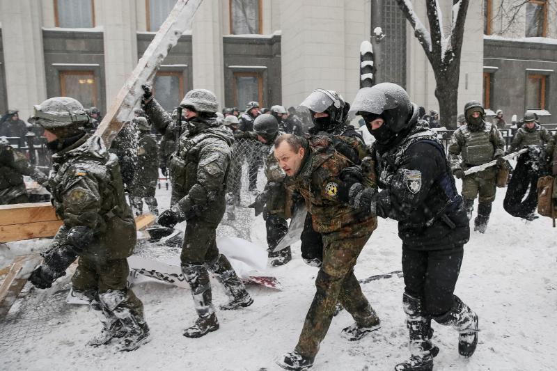 Riot police detain anti-government protesters as service members of the National Guard remove a protest tent camp near the parliament building in Kiev, Ukraine, March 2018.