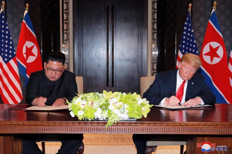 U.S. President Donald Trump and North Korea's leader Kim Jong Un sign documents in Singapore, June 2018.