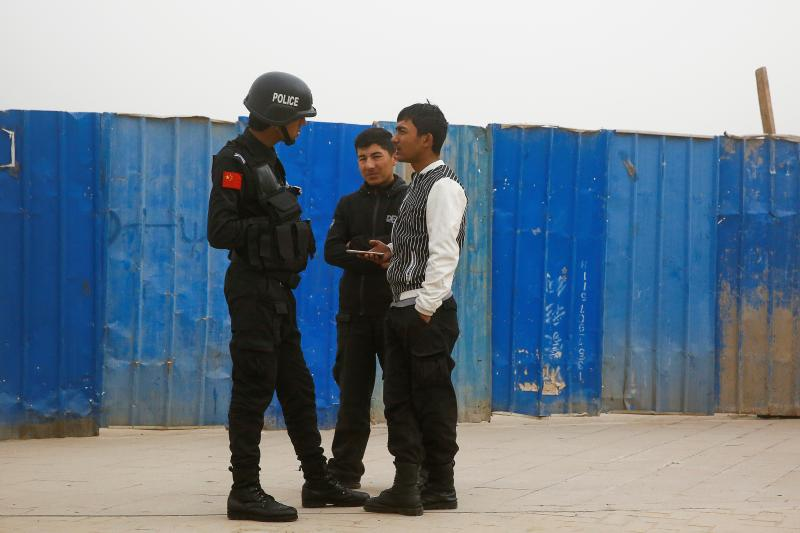 A police officer talks to men in a street in Kashgar, Xinjiang Uighur Autonomous Region, China, March 2017.