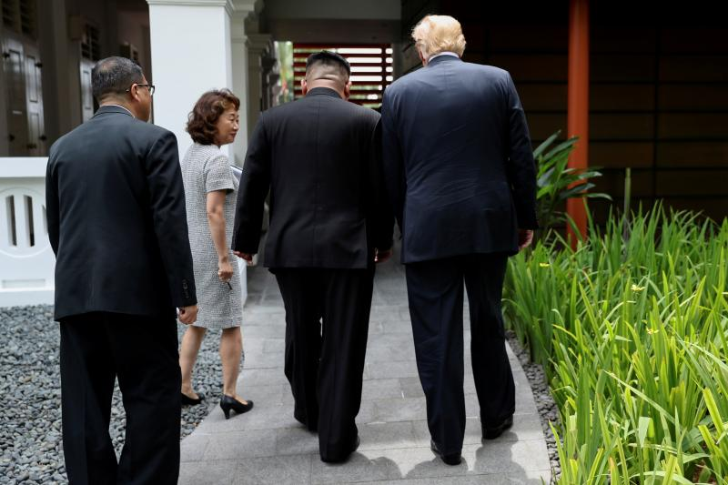U.S. President Donald Trump and North Koreab leader Kim Jong Un walk together before their working lunch during their summit at the Capella Hotel in Singapore, June 2018.