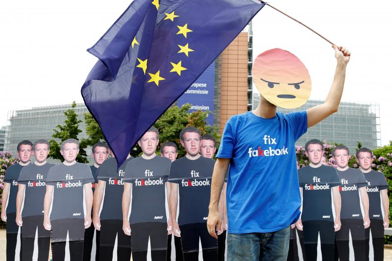 A protestor holds an EU flag next to cardboard cutouts depicting Mark Zuckerberg ahead of a meeting between Zuckerberg and leaders of the European Parliament in Brussels, Belgium, May 2018