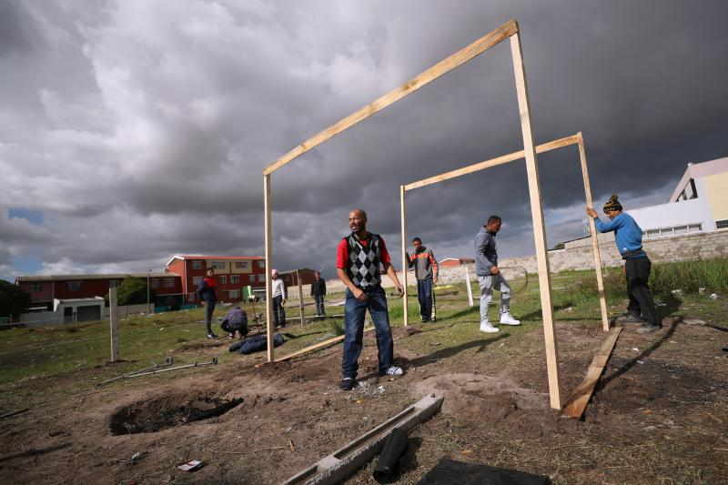 People erect a shack during illegal land occupations, in Mitchell's Plain township near Cape Town, South Africa, May 29, 2018.