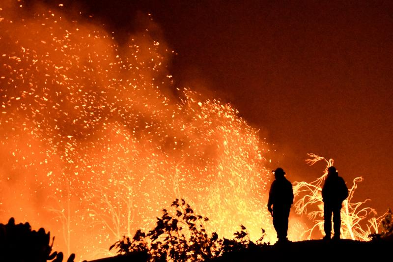 Firefighters keep watch on the Thomas wildfire in the hills and canyons outside Montecito, California, December 2017.