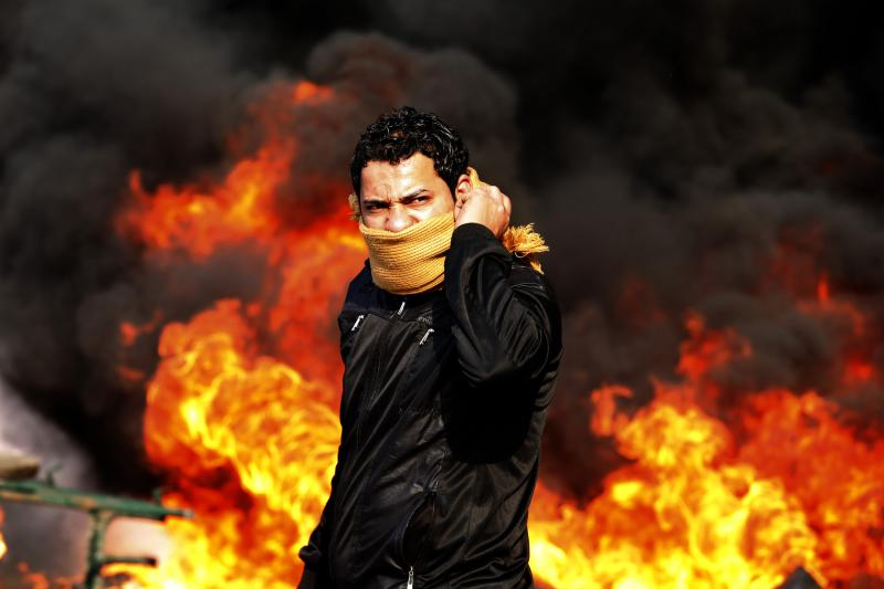 A protester stands in front of a burning barricade during a demonstration in Cairo, Egypt, January 2011
