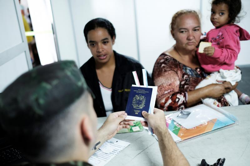 A military officer delivers a Venezuelan family their passports as they apply for refugee status at the Pacaraima border control station in Roraima State, Brazil, August 2018