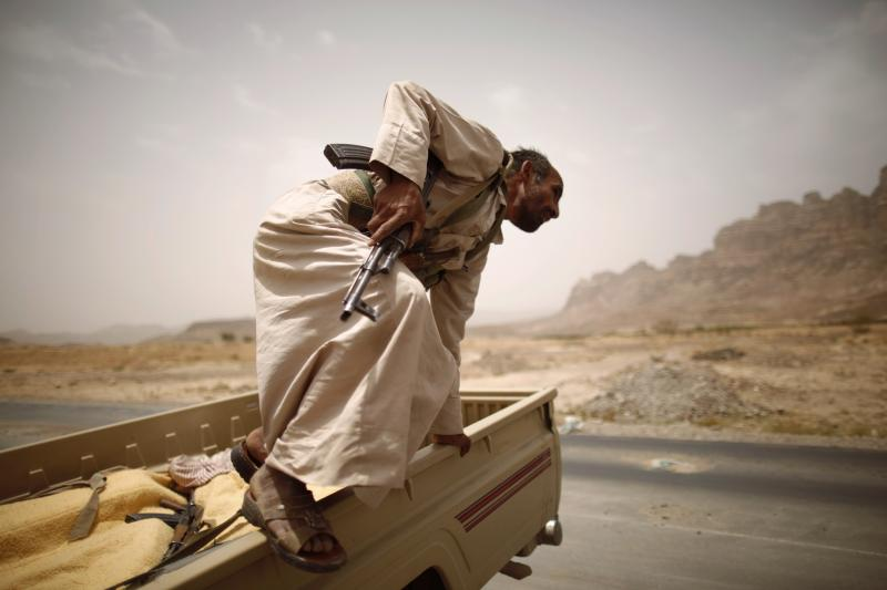 A fighter jumps off a truck on the road between Sana'a and Marib in Yemen, June 25, 2012