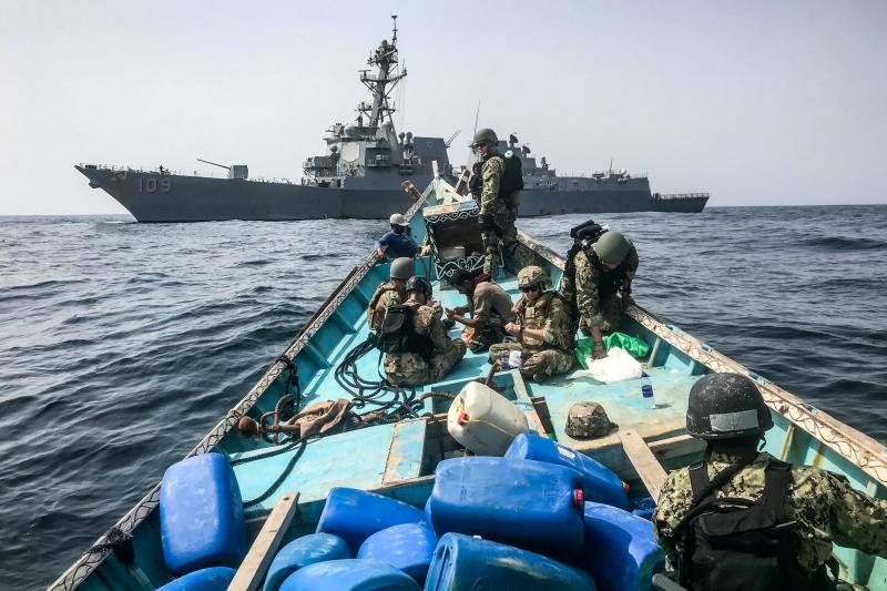 A search and seizure team from the guided-missile destroyer USS Jason Dunham inspect a traditional dhow carrying a shipment of over 1,000 illicit weapons in the Gulf of Aden, August 2018