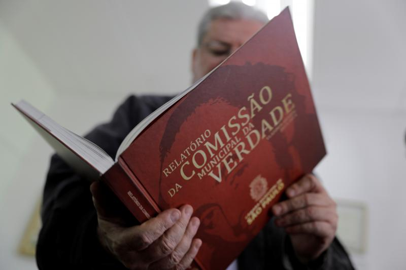 Former political prisoner and Alderman, Gilberto Natalini, holds a book which reports the human rights violations during the military dictatorship in Sao Paulo, Brazil, October 2018.