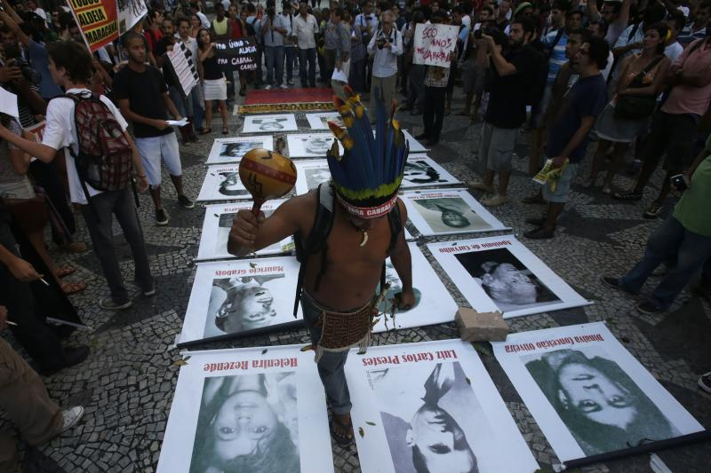 A native Indian walks over pictures of people disappeared during the dictatorship at a protest against the 49th anniversary of the 1964 military coupin Rio de Janeiro, April 2013.