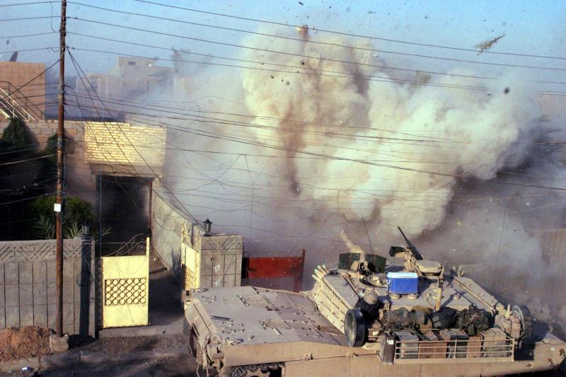 A U.S. M1A1 Abrams tank fires into a building during the Battle of Fallujah, December 2004.