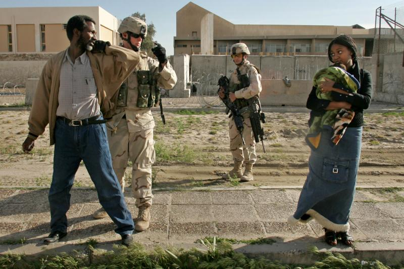 Civilians being searched by U.S. Army soldiers at a traffic checkpoint in Baghdad,March2005