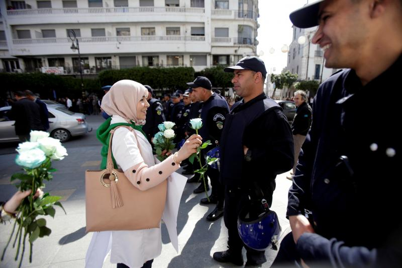 A demonstrator offers a flower to a police officer at a protest in Algiers, Algeria, March 2019