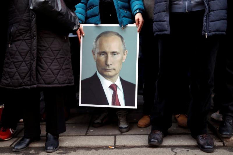 A supporter of Putin holds his portrait in Belgrade, Serbia, January 2019