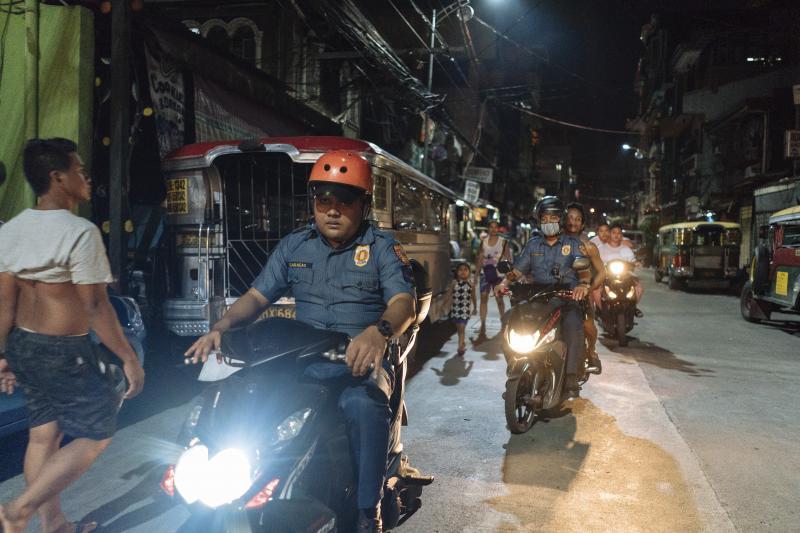 Police officers patrolslums in Manila, June 2018