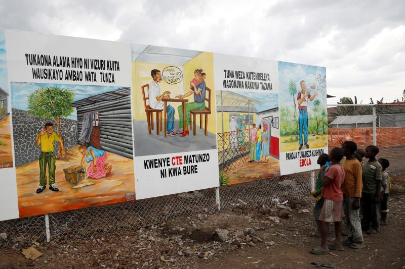 Children look at a billboard providing information about Ebola in the eastern Democratic Republic of Congo, August2019