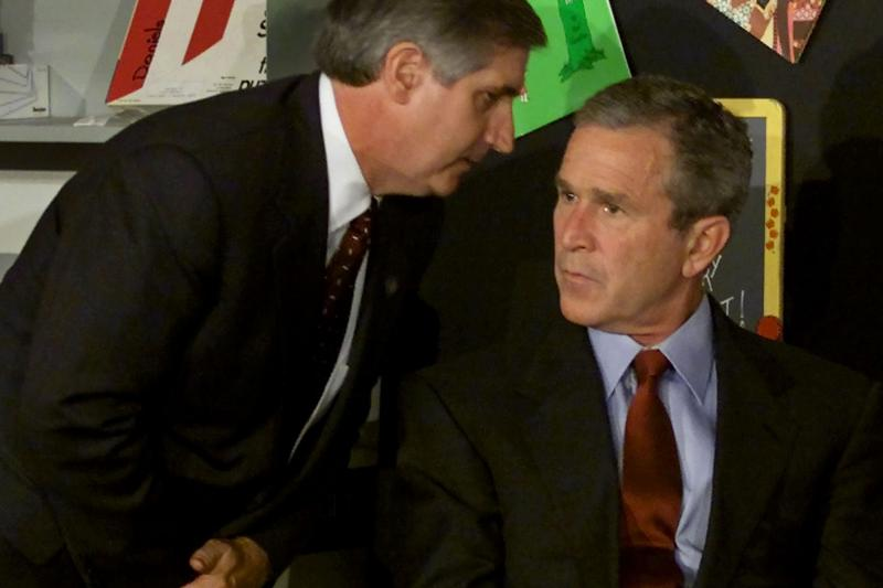 President Bush listens as White House Chief of Staff Andrew Card informs him of a second plane hitting the World Trade Center in Florida, September 11, 2001.