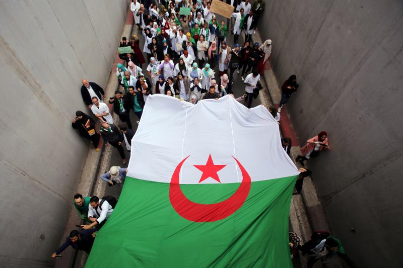 Health workers carry a national flag as they march during a protest calling on President Abdelaziz Bouteflika to quit, in Algiers, Algeria March 19, 2019.