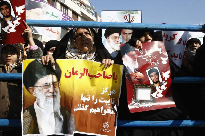 An Iranian woman holds a poster of Iran's Supreme Leader Ayatollah Ali Khamenei as they attend a pro-government rally in Tehran, February 2011.