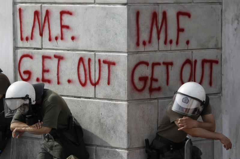 Greek riot policemen rest in front of graffiti written on the wall of a bank during violent demonstrations over austerity measures in Athens, May 2010.