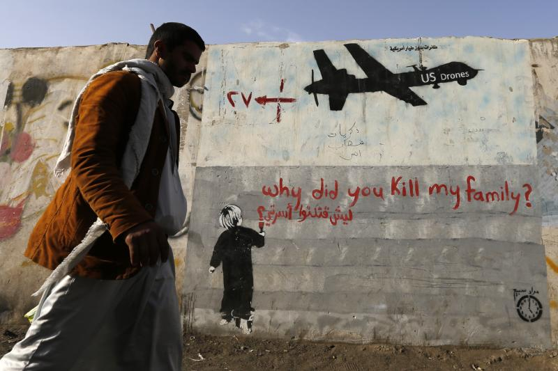 A man walks past graffiti, denouncing strikes by U.S. drones in Yemen, painted on a wall in Sanaa, Yemen, November 2014.