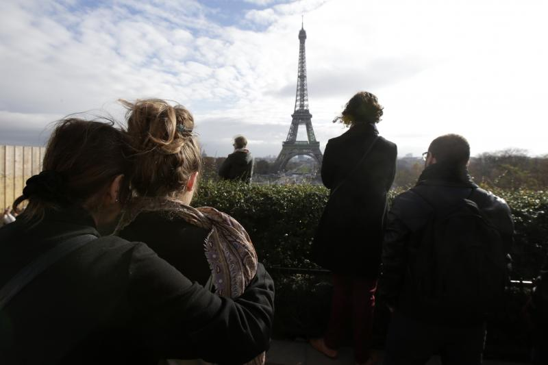 People observe a moment of silence near the Eiffel Tower to commerate the victims of terrorist attacks in France, November 2015.