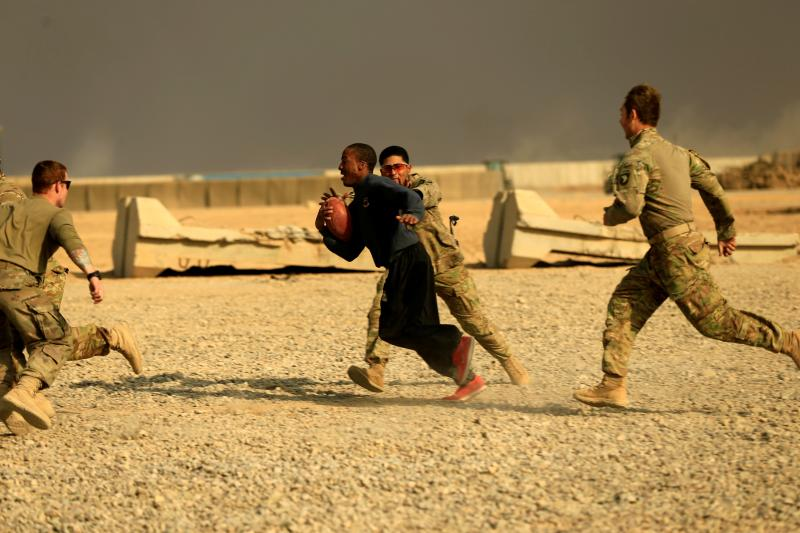 U.S. soldiers play football on Thanksgiving Day inside the army base in Qayyara, Iraq, November 2016.