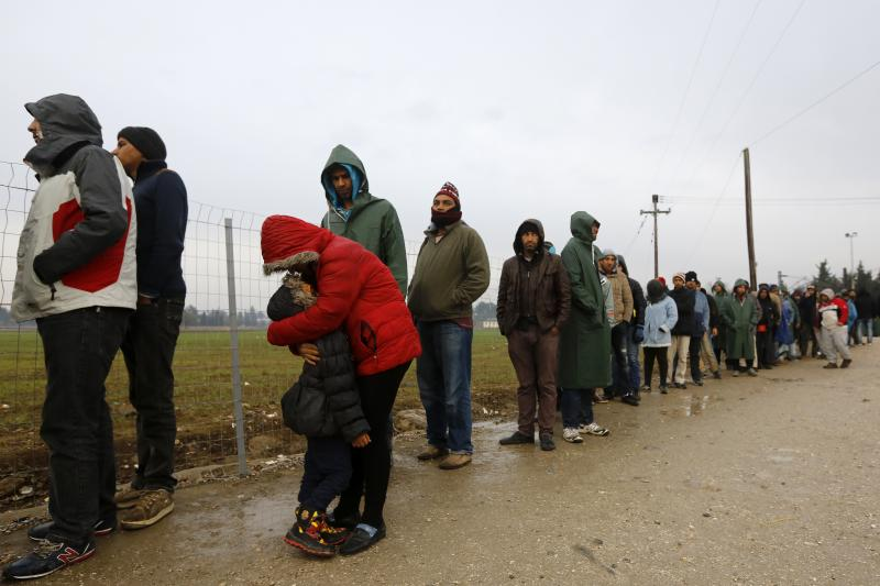 A stranded Iranian woman embraces her daughter as hundreds of migrants line up during food distribution at the Greek-Macedonian border, near the Greek village of Idomeni, November 2015.