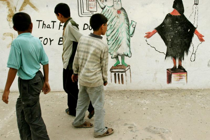 Wall paintings based on the Abu Ghraib prisoner abuse scandal in Baghdad's Sadr city, May 2004.
