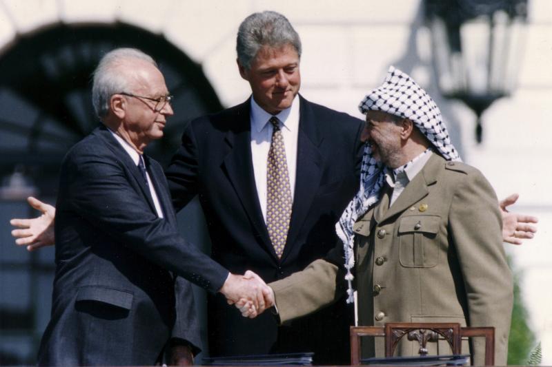 Israeli Prime Minister Yitzhak Rabin (L) shakes hands with PLO Chairman Yasir Arafat in front of U.S. President Bill Clinton, September 1993.