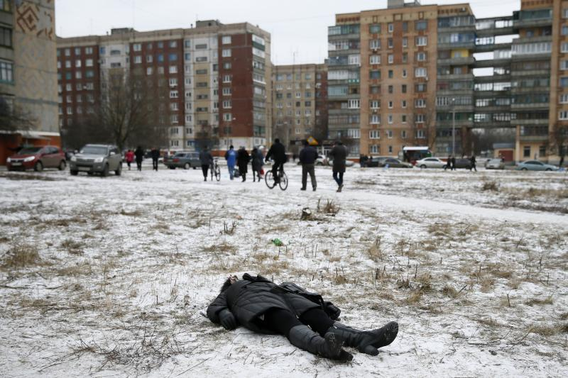 The body of a woman killed by recent shelling lies in a street in Kramatorsk, in eastern Ukraine, February 2015.