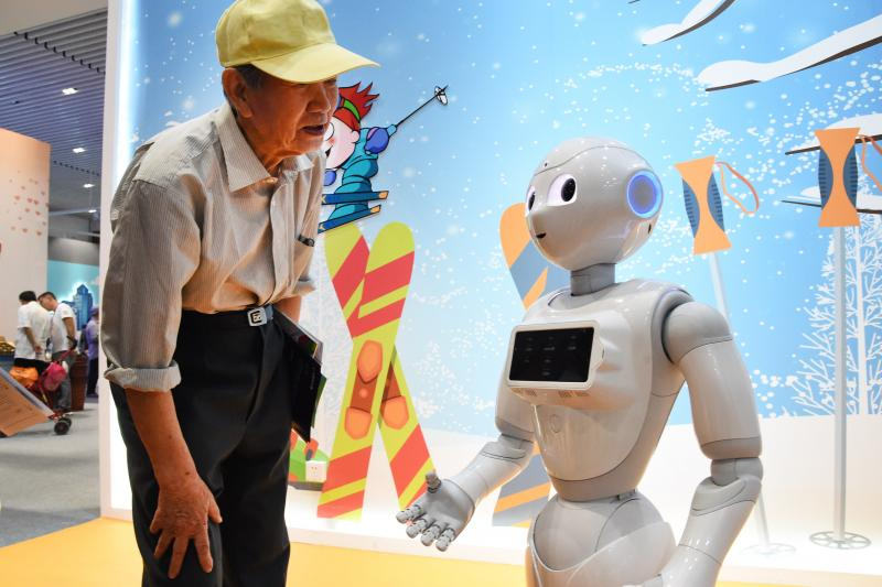 A man interacts with a cloud-based intelligent robot in Beijing, China, May 2019