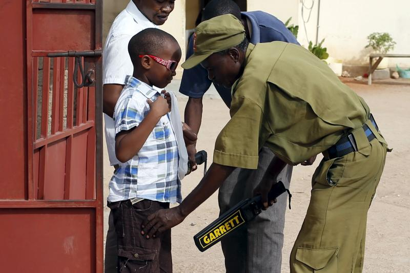 A boy is searched for weapons in front of a Catholic church in Garissa, April 5, 2015.