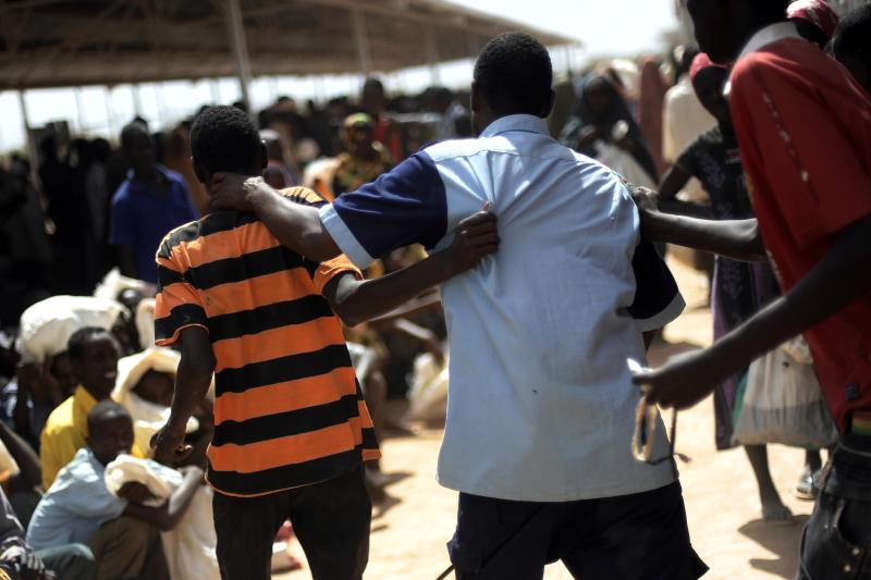 A guard collars a Somali refugee after he tried to jump the line at the World Food Program distribution center in Dadaab Camp.