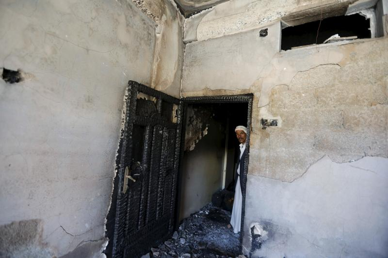 A man looks at damage in his house caused by an air strike that hit a nearby army weapons depot in Sanaa, April 18, 2015.