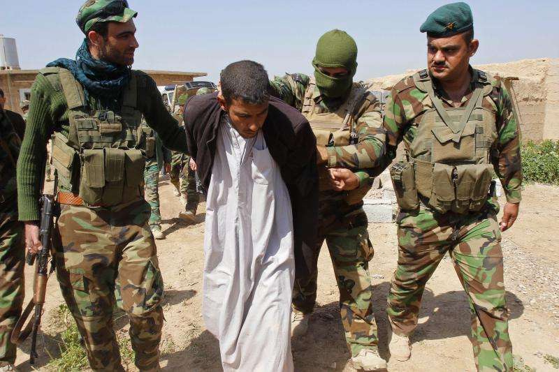 Members of the Kurdish peshmerga forces detain a man suspected of having links to the Islamic State, on the outskirts of Kirkuk