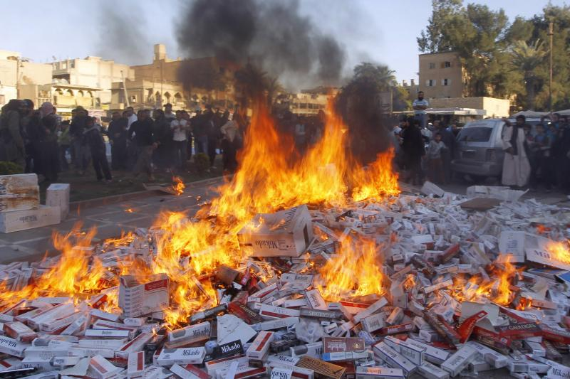 ISIS fighters burn confiscated cigarettes in the city of Raqqa, April 2, 2014.