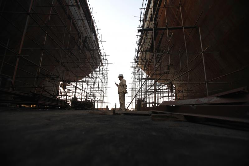 A laborer looks at his phone as he takes a break from work at a shipyard in Yueqing City, Zhejiang Province March 27, 2012.