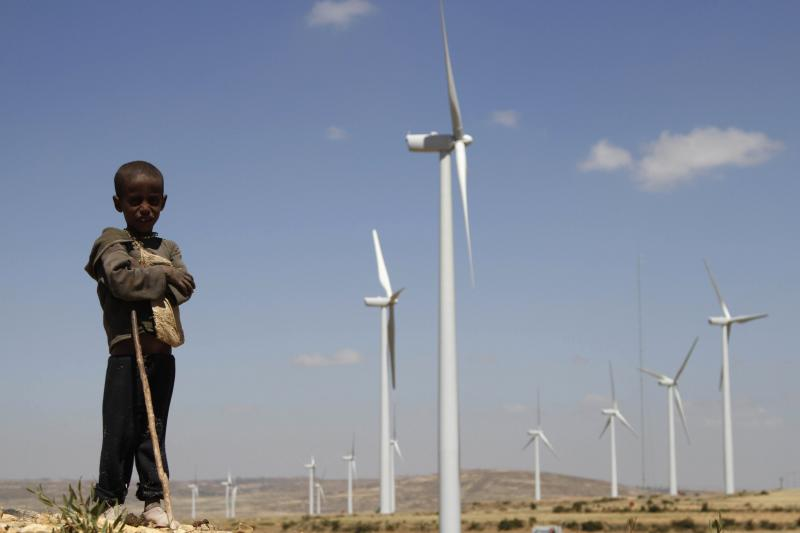 A boy stands in front of wind turbines at the Ashegoda Wind Farm 485 miles north of Addis Ababa, October 25, 2013.