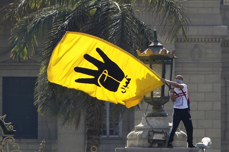 A Morsi supporter waves a flag bearing the Rabaa, May 2014.