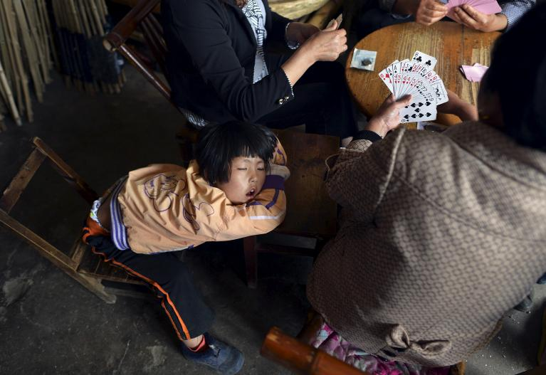A girl sleeps as her family members play cards inside a small shop in Tongcheng, Anhui province, China, May 13, 2015.